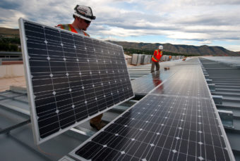 Workers putting on solar panels
