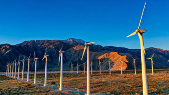 wind turbines in desert with mountains